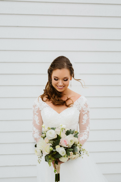 outer banks bride looking at her flowers on her wedding day